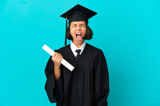 Young university graduate girl over isolated blue background shouting to the front with mouth wide open