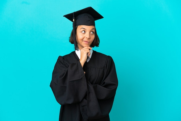 Young university graduate girl over isolated blue background thinking an idea while looking up