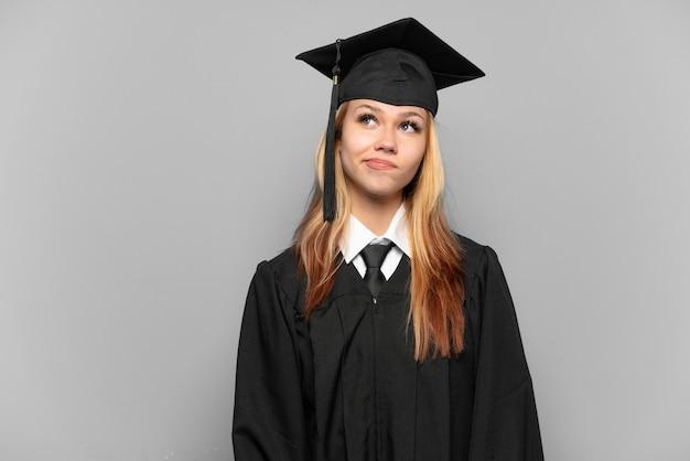 孤立した背景と見上げる上の若い大学卒業生の女の子