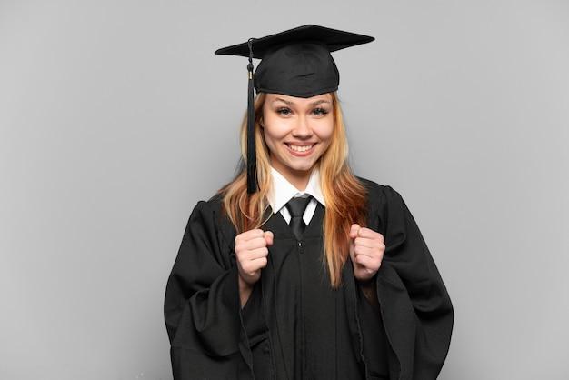 Молодая выпускница университета на изолированном фоне празднует победу в победном положении