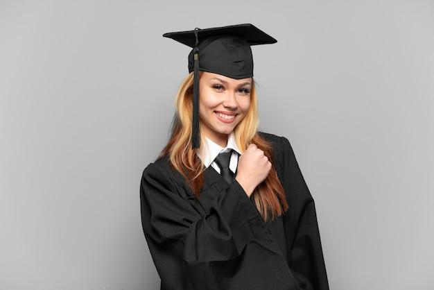 Девушка-выпускница университета на изолированном фоне празднует победу