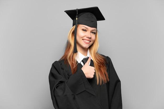 Молодая девушка-выпускница университета на изолированном фоне, показывая жест пальца вверх