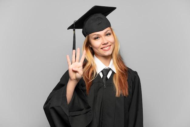 Молодая выпускница университета на изолированном фоне счастлива и считает четыре пальцами