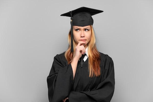 疑問と思考を持っている孤立した背景上の若い大学卒業生の女の子