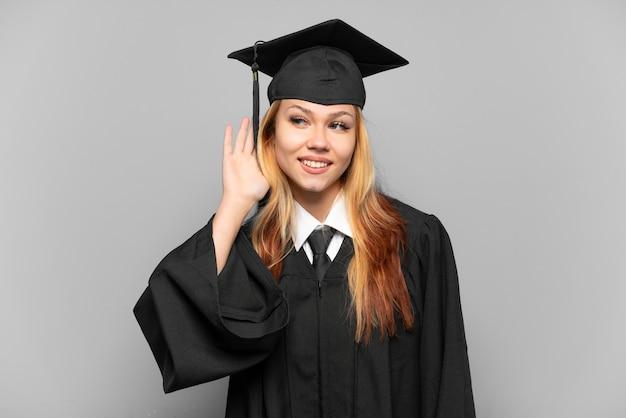 Молодая девушка-выпускница университета на изолированном фоне слушает что-то, положив руку на ухо