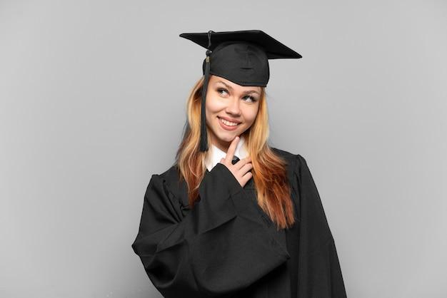 Молодая девушка-выпускница университета на изолированном фоне, глядя вверх, улыбаясь