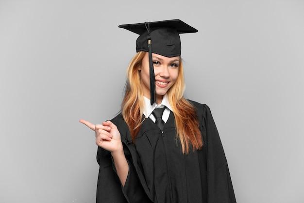 横に指を指している孤立した背景上の若い大学卒業生の女の子