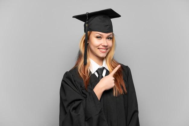 제품을 제시하기 위해 측면을 가리키는 격리 된 배경 위에 젊은 대학 대학원 소녀