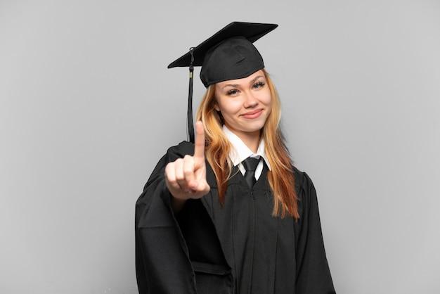 Молодая девушка-выпускница университета на изолированном фоне, показывая и поднимая палец