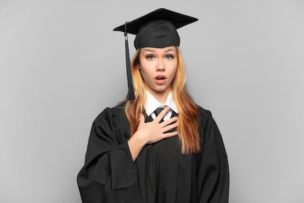 고립된 배경 위에 있는 젊은 대학 대학원 소녀는 오른쪽을 바라보면서 놀라고 충격을 받았습니다.