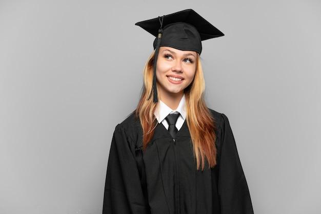 見上げながらアイデアを考えている孤立した背景上の若い大学卒業生の女の子
