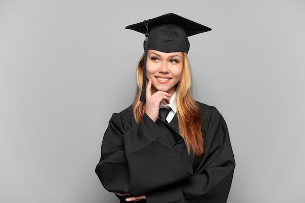찾는 동안 아이디어를 생각하는 격리 된 배경 위에 젊은 대학 대학원 소녀