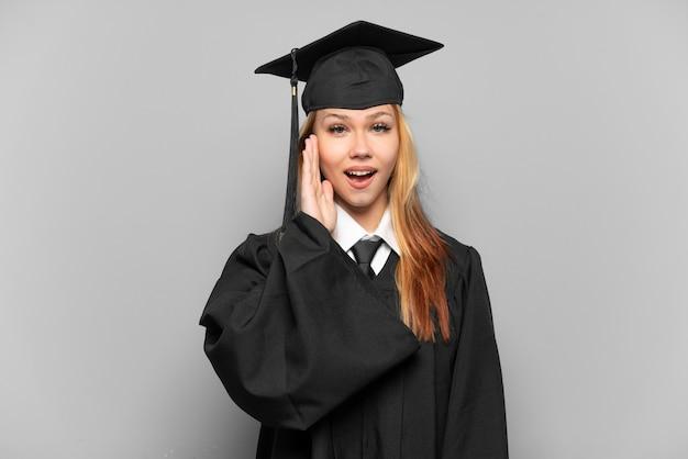 Молодая выпускница университета на изолированном фоне с удивленным и шокированным выражением лица