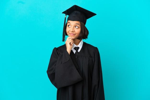 고립 된 파란색 배경 위에 젊은 대학 대학원 소녀와 찾고