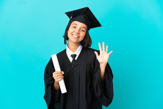 손가락으로 다섯을 세는 고립 된 파란색 배경 위에 젊은 대학 대학원 소녀