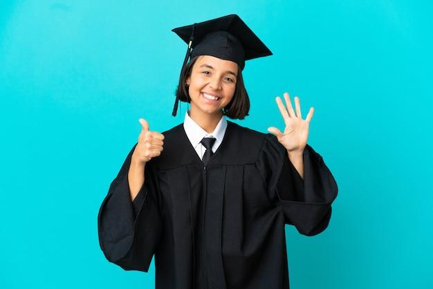Молодая выпускница университета на изолированном синем фоне, считая шесть пальцами
