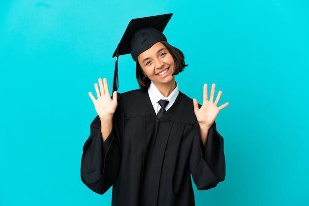 손가락으로 10을 세는 고립 된 파란색 배경 위에 젊은 대학 대학원 소녀
