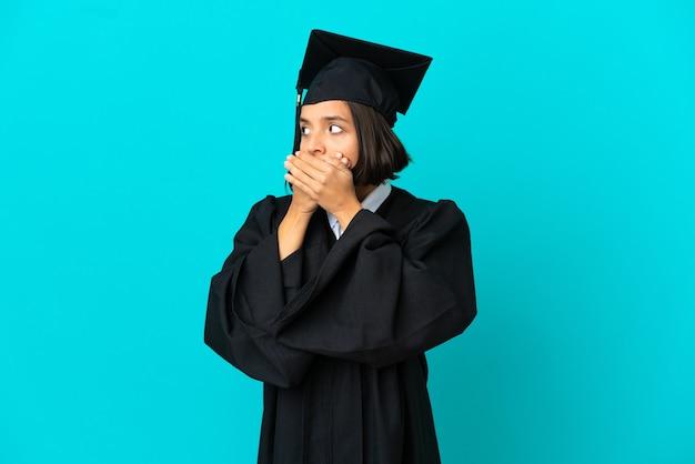 입을 가리고 옆을 바라보는 고립된 파란색 배경 위에 젊은 대학 대학원 소녀