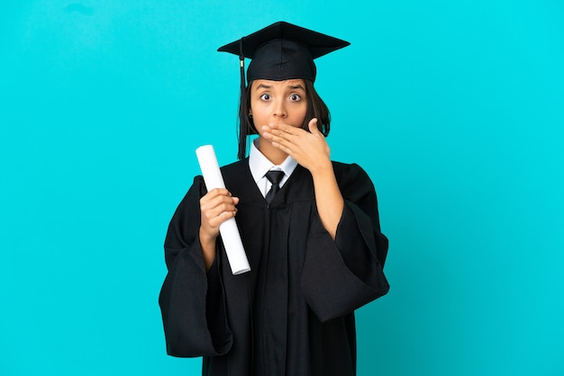 Молодая девушка-выпускница университета на изолированном синем фоне, прикрывая рот руками