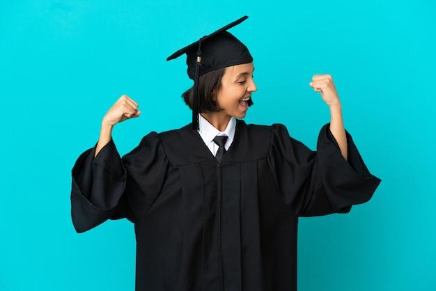 Девушка-выпускница университета на изолированном синем фоне делает сильный жест