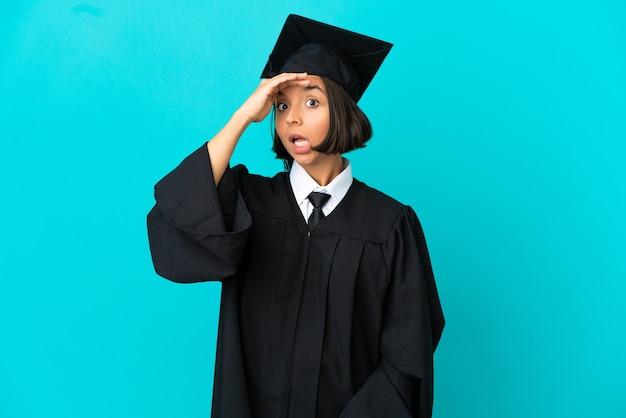 横を見ながら驚きのジェスチャーをしている孤立した青い背景の上の若い大学卒業生の女の子
