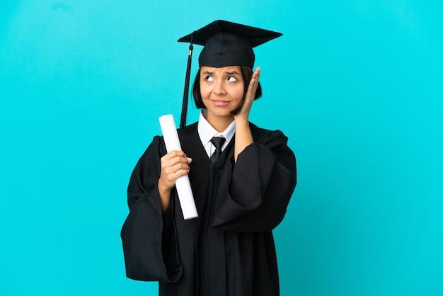 欲求不満と耳を覆っている孤立した青い背景の上の若い大学卒業生の女の子