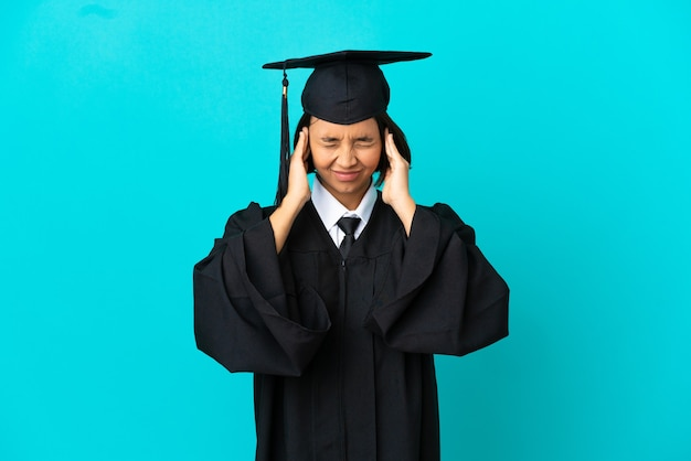 Молодая выпускница университета на изолированном синем фоне расстроена и закрывает уши