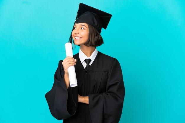 孤立した青い背景の上の若い大学卒業生の女の子幸せと笑顔