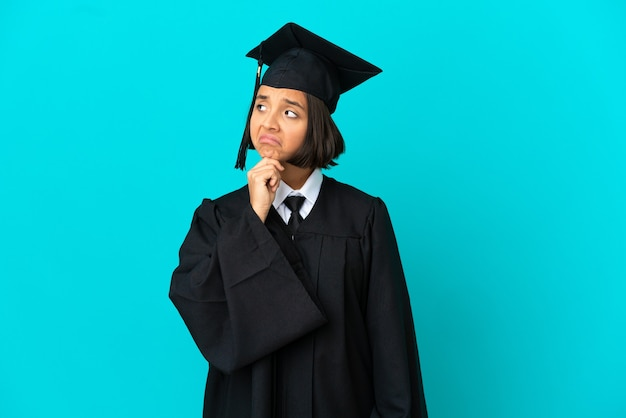 의심을 품고 고립된 파란색 배경 위에 젊은 대학 대학원 소녀