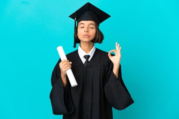 선 포즈에서 고립 된 파란색 배경 위에 젊은 대학 대학원 소녀