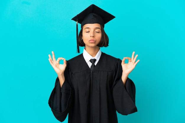 Молодая выпускница университета на изолированном синем фоне в позе дзен