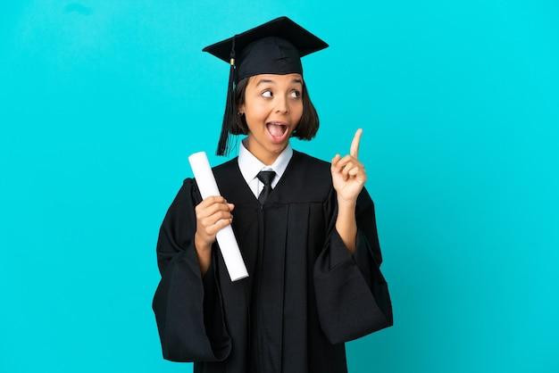 격리된 파란색 배경 위에 있는 젊은 대학 대학원 소녀는 손가락을 들어올리면서 솔루션을 실현하려고 합니다.