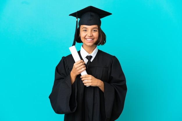 Девушка-выпускница университета на изолированном синем фоне смеется