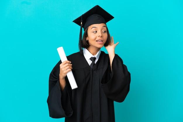 귀에 손을 대고 뭔가를 듣고 고립 된 파란색 배경 위에 젊은 대학 대학원 소녀