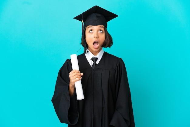 Молодая девушка-выпускница университета на изолированном синем фоне смотрит вверх и с удивленным выражением лица