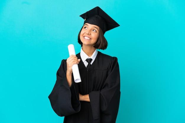 Молодая девушка-выпускница университета на изолированном синем фоне, глядя вверх, улыбаясь