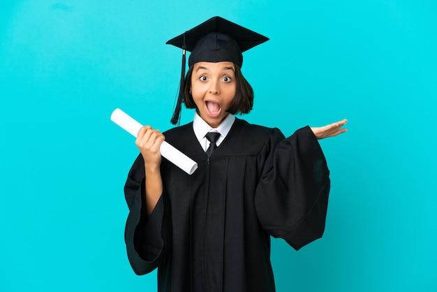 Молодая выпускница университета на изолированном синем фоне, делая жест сомнения