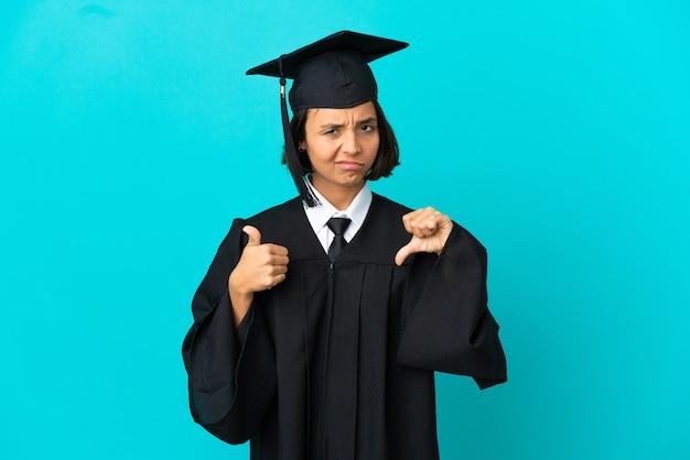 Молодая девушка выпускник университета на изолированном синем фоне, делая знак