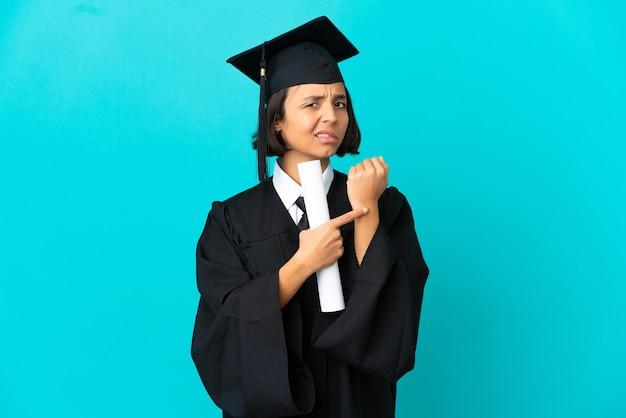 고립 된 파란색 배경 위에 늦는 제스처를 만드는 젊은 대학 대학원 소녀