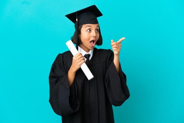 Молодая девушка-выпускница университета на изолированном синем фоне, указывая в сторону