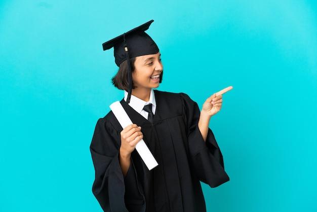 외진 파란색 배경 위에 손가락을 옆으로 가리키고 제품을 제시하는 젊은 대학 대학원생