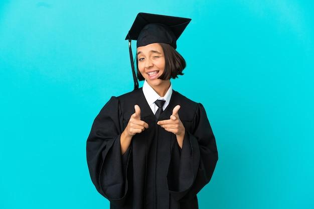 Молодая девушка-выпускница университета на изолированном синем фоне, указывая на фронт и улыбаясь