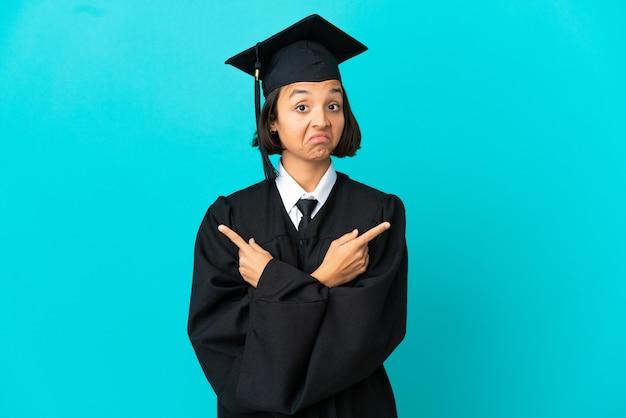 Молодая девушка-выпускница университета на изолированном синем фоне, указывая на боковые стволы, сомневаясь