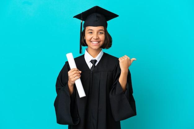 제품을 제시하기 위해 측면을 가리키는 고립된 파란색 배경 위에 젊은 대학 대학원 소녀