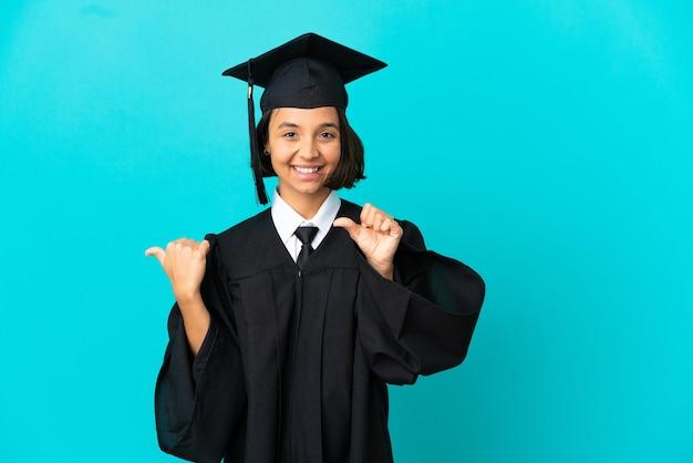 Молодая девушка-выпускница университета на изолированном синем фоне, указывая в сторону, чтобы представить продукт