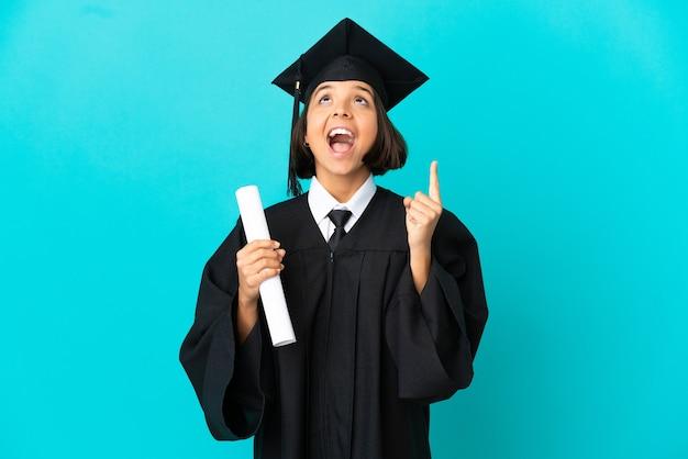 Молодая девушка-выпускница университета на изолированном синем фоне, указывая вверх и удивленная