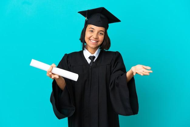 격리된 파란색 배경을 가진 젊은 대학 대학원 소녀가 프레젠테이션을 하고 손을 잡고 초대합니다.