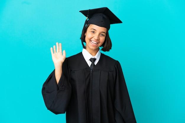 Молодая выпускница университета на изолированном синем фоне, салютуя рукой с счастливым выражением лица