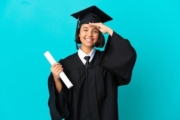 행복 한 표정으로 손으로 경례 고립 된 파란색 배경 위에 젊은 대학 대학원 소녀