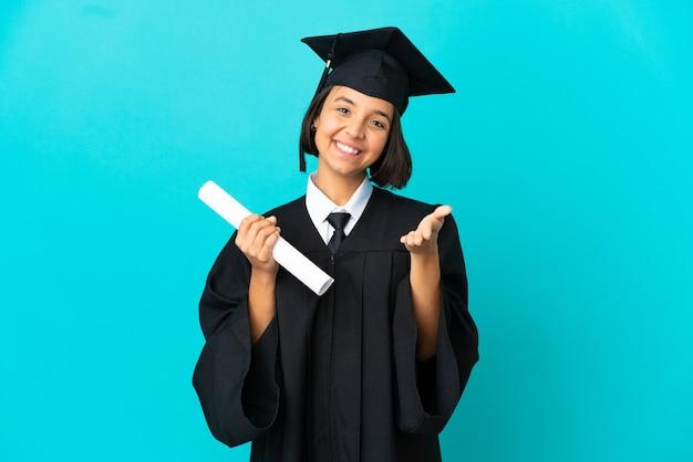 좋은 거래를 성사시키기 위해 악수하는 고립된 파란색 배경 위에 젊은 대학 대학원 소녀